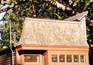 scalloped, or fishscale shingle roof, capping the stained-glass windows.