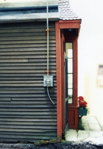 Alley side of the building with shiplap siding and water meter